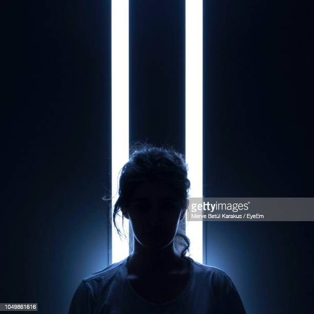 silhouette woman standing against illuminated lighting equipment in darkroom - darkroom stock pictures, royalty-free photos & images