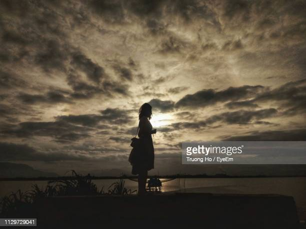 silhouette woman standing against lake during sunset - pretty vietnamese women stock pictures, royalty-free photos & images