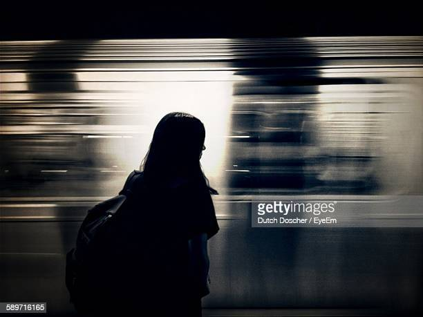 Silhouette Woman Standing Against Moving Train At Night
