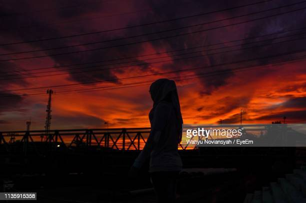 Silhouette Woman Standing Against Sky During Sunset