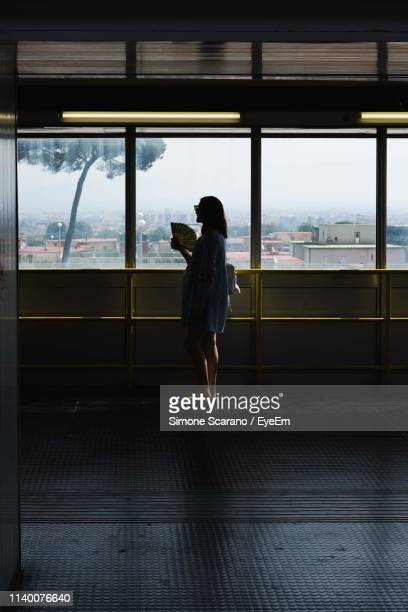 silhouette woman standing against window - one young woman only stock pictures, royalty-free photos & images