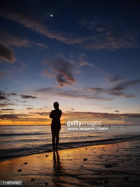 silhouette woman standing at beach against sky during sunset - marine jacquemin stock pictures, royalty-free photos & images