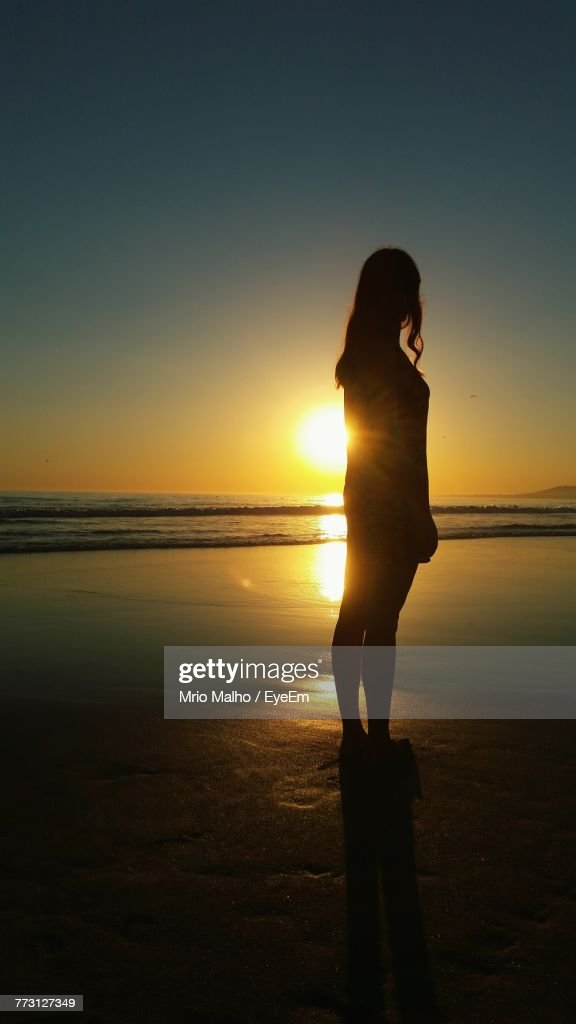Silhouette Woman Standing At Beach Against Sky During Sunset : Photo