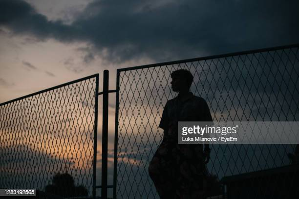 silhouette woman standing by fence against sky during sunset - chainlink fence stock pictures, royalty-free photos & images