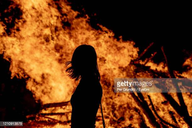 silhouette woman standing by fire at night - burning stock pictures, royalty-free photos & images