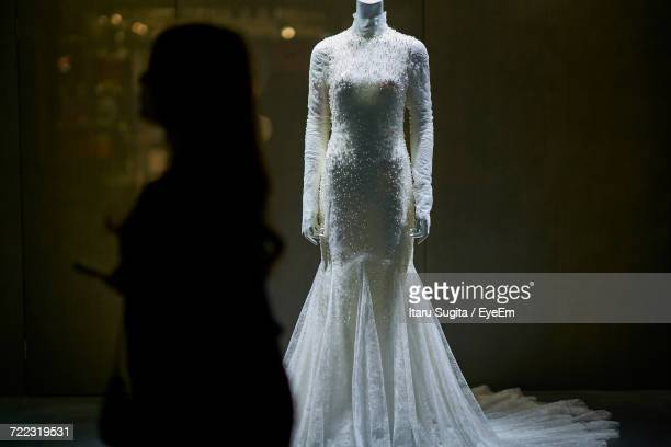 Silhouette Woman Standing By Mannequins In Wedding Dress At Bridal Shop