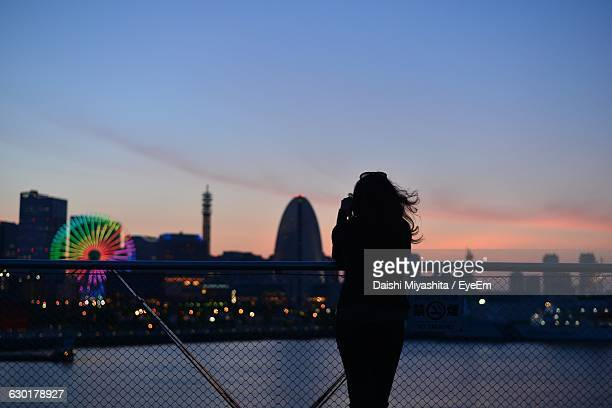 Silhouette Woman Standing By Railing At Minato Mirai Against Sky