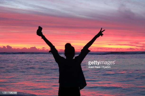 silhouette woman standing by sea against colorful sky during sunset - 雰囲気 ストックフォトと画像