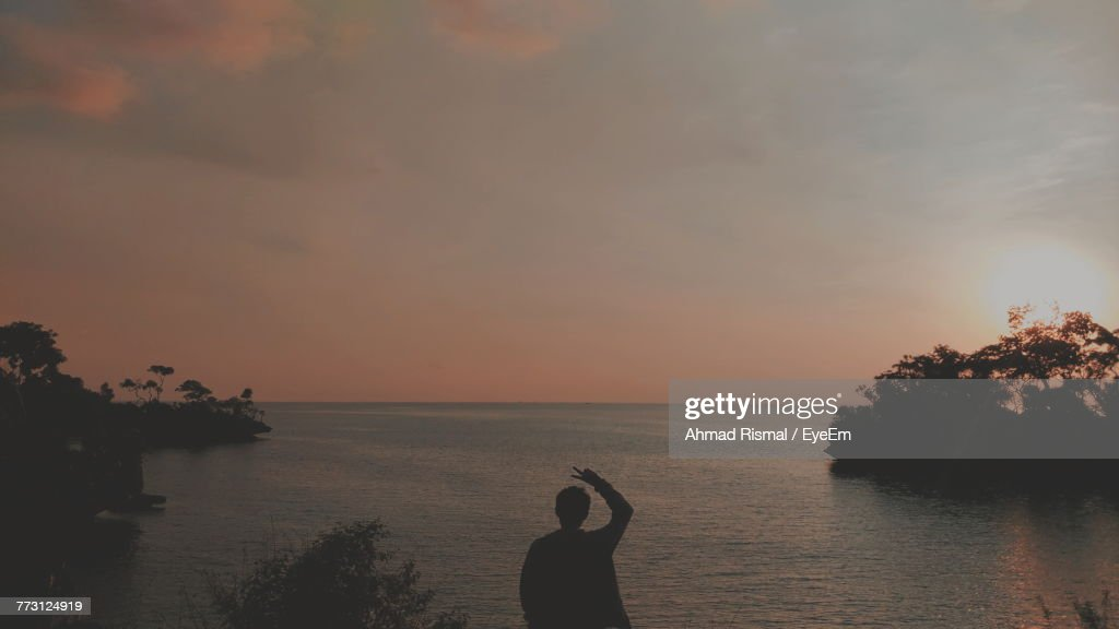 Silhouette Woman Standing By Sea Against Sky During Sunset : Photo