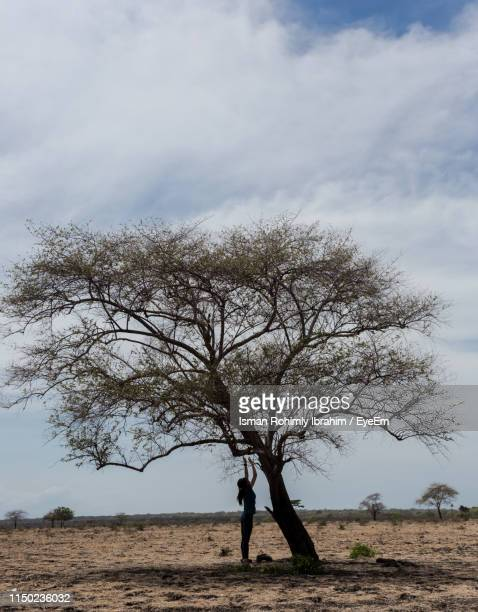 Silhouette Woman Standing By Tree On Field Against Cloudy Sky