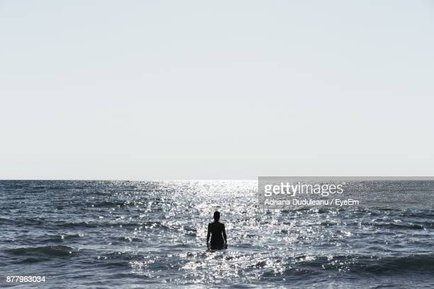 silhouette woman standing in sea against clear sky - adriana duduleanu stock photos and pictures