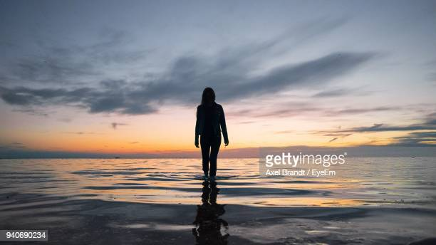silhouette woman standing in sea against sky during sunset - wading stock pictures, royalty-free photos & images