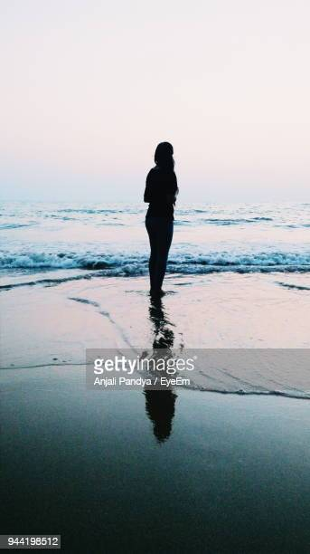 Silhouette Woman Standing On Beach Against Clear Sky