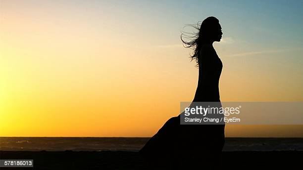 silhouette woman standing on beach during sunset - silhouette femme photos et images de collection