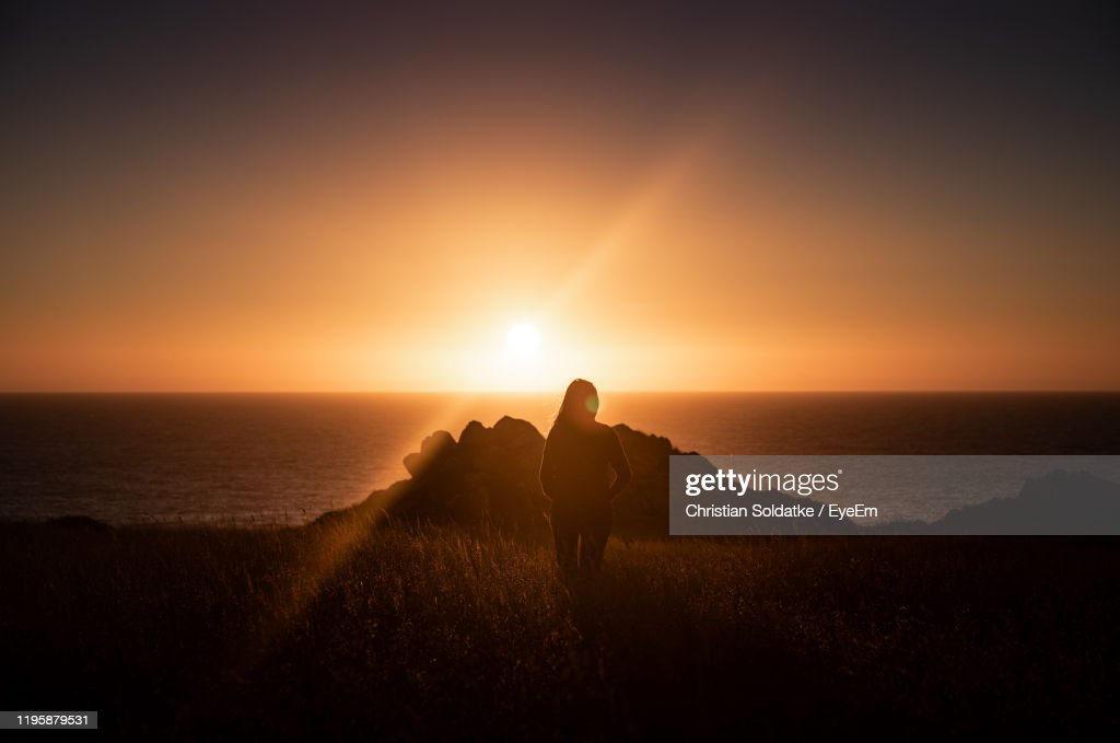 Silhouette Woman Standing On Land Against Sea And Sky During Sunset : Stock-Foto
