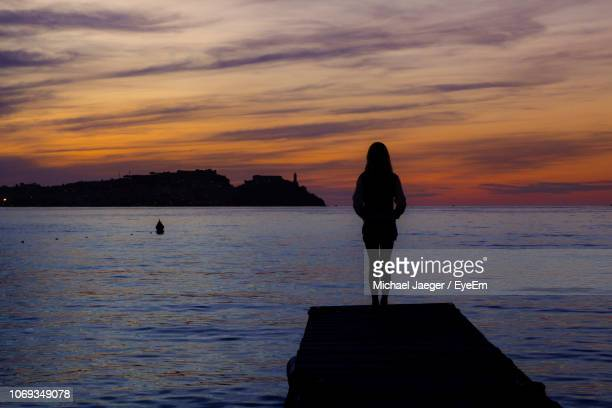 silhouette woman standing on pier against sky during sunset - michael jaeger stock pictures, royalty-free photos & images