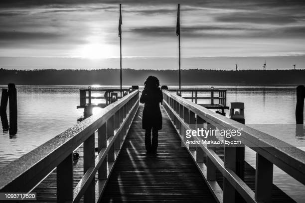 Silhouette Woman Standing On Pier Over Sea During Sunset