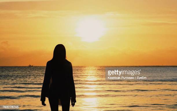 Silhouette Woman Standing On Shore At Beach Against Orange Sky During Sunset