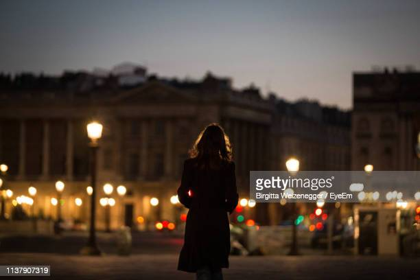 silhouette woman standing on street in city at night - paris france photos et images de collection