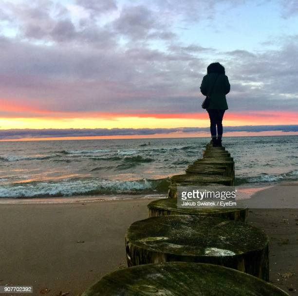 silhouette woman standing on wooden post at beach against sky during sunset - swiatek stock pictures, royalty-free photos & images