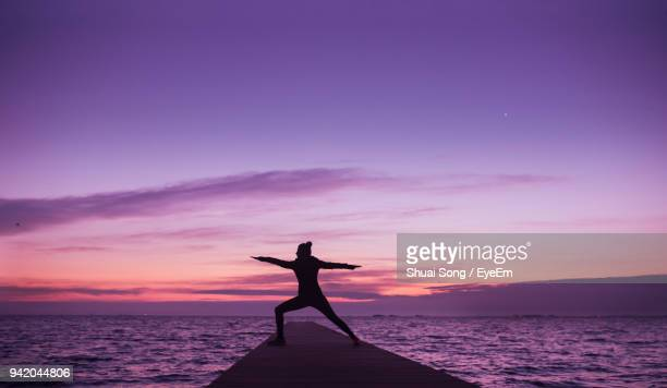 silhouette woman standing pier by sea against sky during sunset - violet photos et images de collection