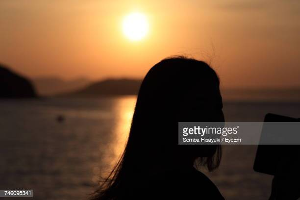 Silhouette Woman Using Mobile Phone By Sea Against Sky During Sunset