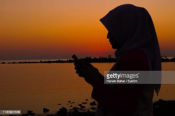 silhouette woman using phone while standing at beach against orange sky - muslim woman beach stock photos and pictures