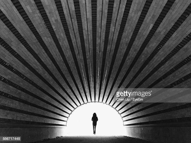 silhouette woman walking in tunnel - symmetry stock pictures, royalty-free photos & images