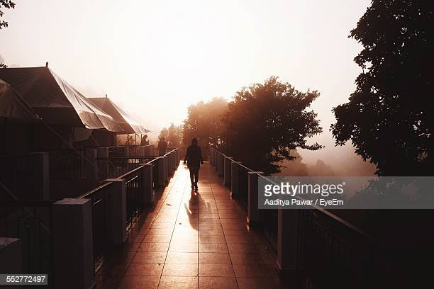 Silhouette Woman Walking On Bridge On Sunny Day Against Clear Sky