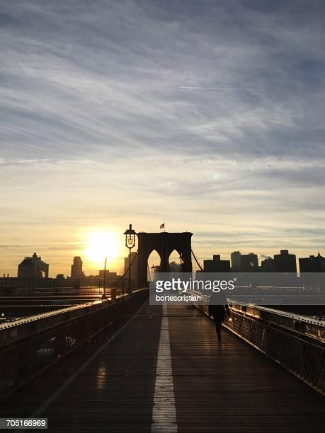 silhouette woman walking on brooklyn bridge against sky during sunset - bortes imagens e fotografias de stock
