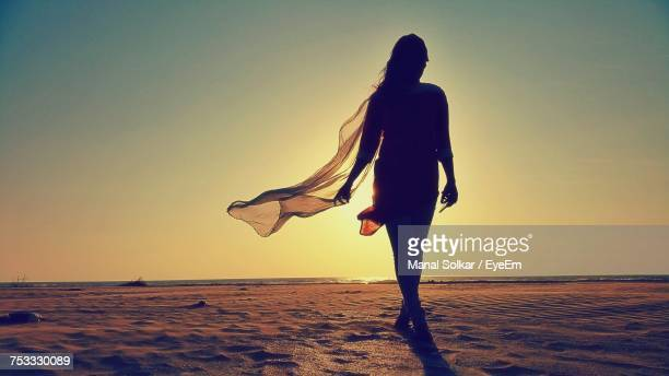 silhouette woman walking on sand at beach against sky during sunny day - salwar kameez stock pictures, royalty-free photos & images
