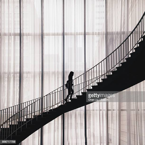 silhouette woman walking on staircase in building - ladder of success stock pictures, royalty-free photos & images