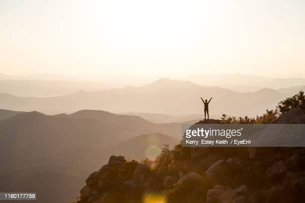 silhouette woman with arm raised standing on mountain against sky during sunset - kerry estey keith stock photos and pictures