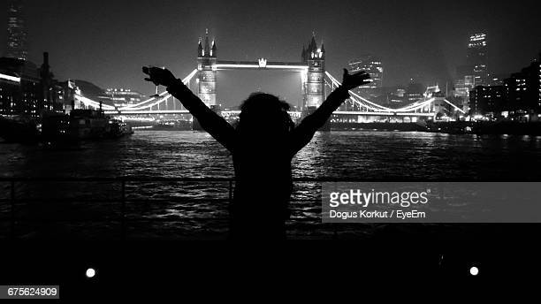 Silhouette Woman With Arms Outstretched Against Illuminated Tower Bridge At Night