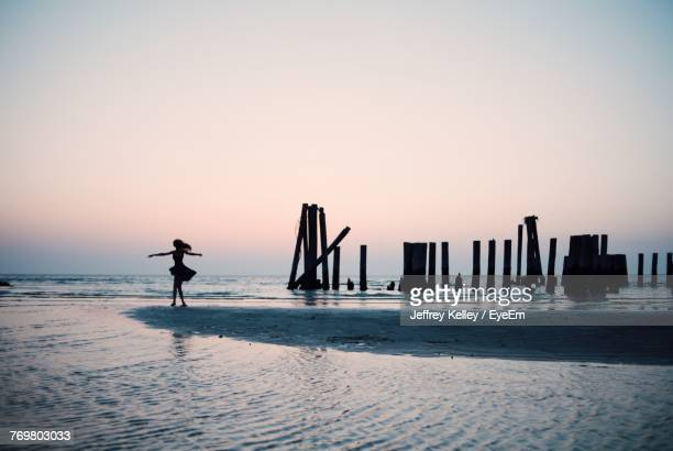Silhouette Woman With Arms Outstretched Standing At Beach During Sunset