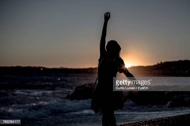 Silhouette Woman With Hand Raised Standing At Beach Against Sky During Sunset