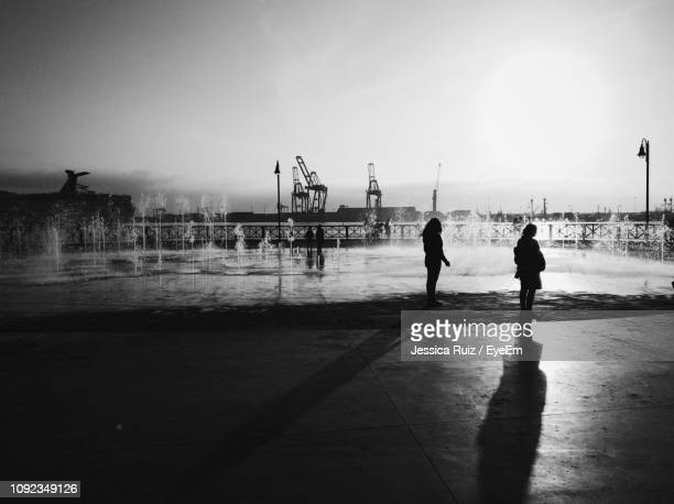silhouette women standing by fountain against sky - mexico black and white stock pictures, royalty-free photos & images