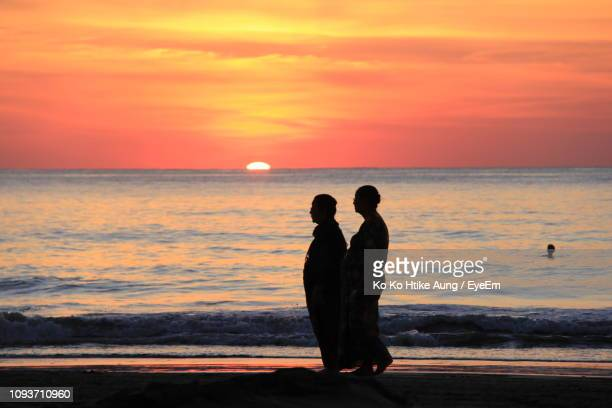 silhouette women walking at beach during sunset - ko ko htike aung stock pictures, royalty-free photos & images