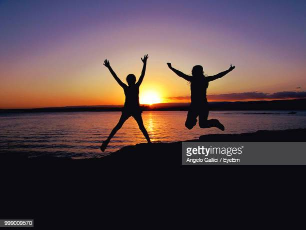 Silhouette Women With Arms Raised Jumping Over Beach Against Sky During Sunset