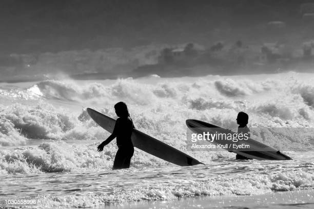 Silhouette Women With Surfboards In Sea