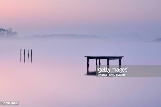 silhouette wooden posts in lake against sky during sunset - andrea rizzi stockfoto's en -beelden