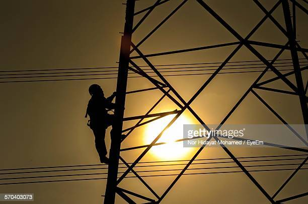 Silhouette Worker Climbing On Electricity Pylon During Sunset