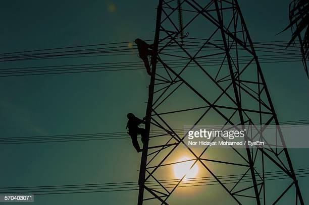 Silhouette Workers Climbing On Electricity Pylon During Sunset