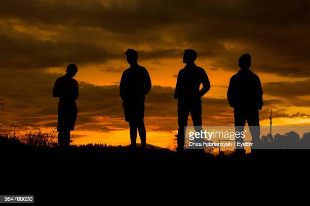 silhouette young friends standing on field against orange sky - four people stock pictures, royalty-free photos & images