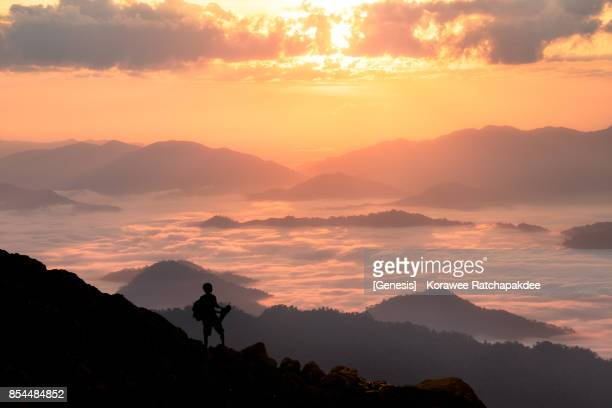 A silhouette young man traveler in the morning sunrise and beautiful nature surround