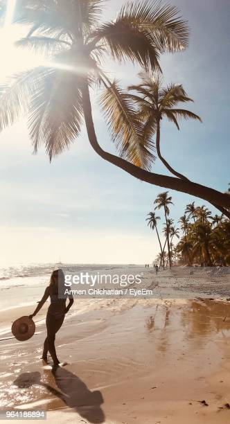 silhouette young woman holding hat while standing at beach against sky during sunny day - punta cana fotografías e imágenes de stock