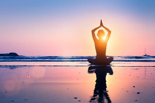 Silhouette young woman practicing yoga lotus position, meditating, beach 875332502