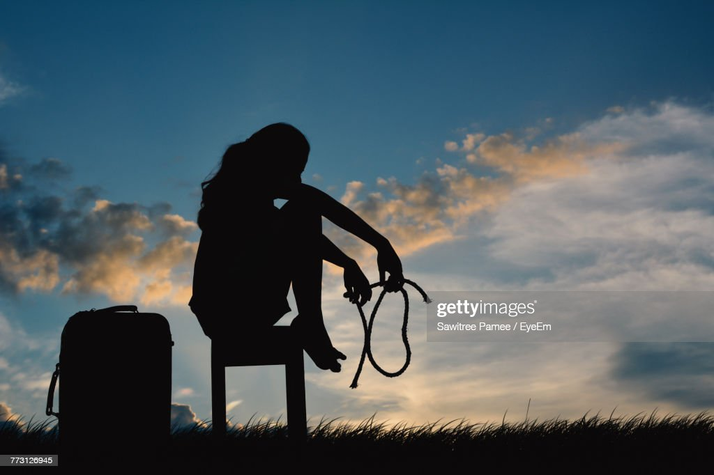Silhouette Young Woman Sitting On Table Against Sky During Sunset : Photo