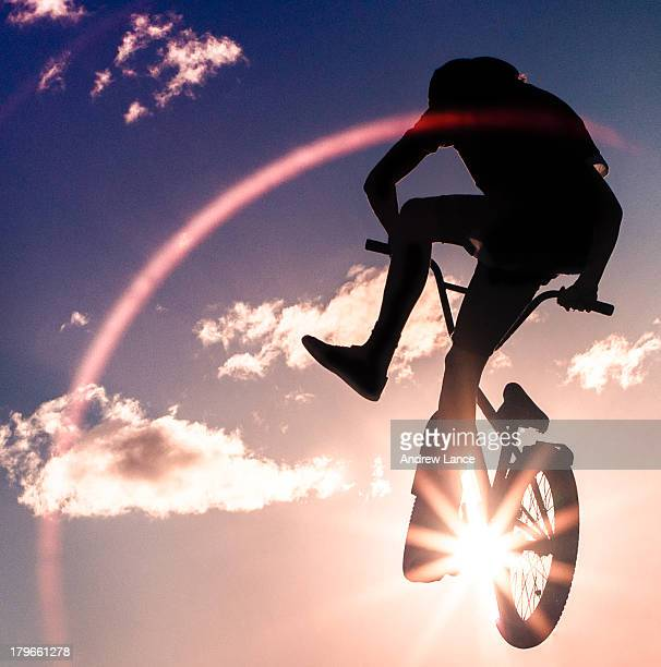 Silhouetted agains the sun, a boy practices jumps on his bike in a dry storm-water drain, Canberra.