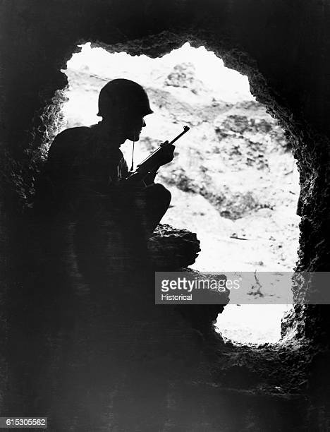 Silhouetted against the entrance to one of the caves that honeycomb the Okinawa hills a Marine rifleman resorts to catandmouse tactics to pick off...